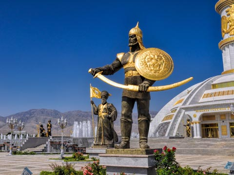 Independence memorial consisting of a warrior in gold armour in a central square of Ashgabat, Turkmenistan