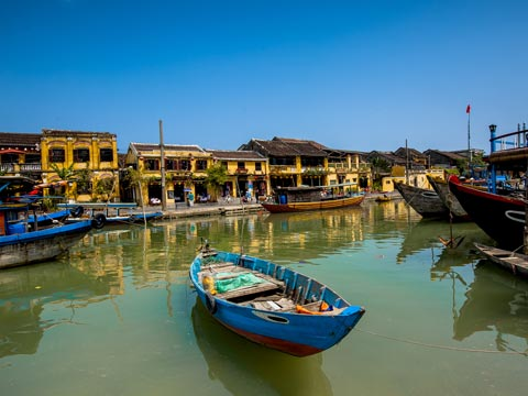 Small ochre coloured buildings overlooking a bright blue fishing boat in the harbour of Hoi An