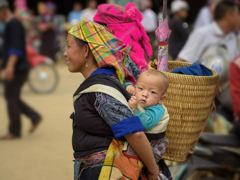 Woman in traditional clothing carrying her baby on her back through a local market