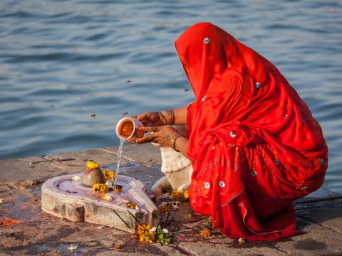 Indian women in red sari crouching down and making an offering beside the Narmada River in Maheshwar