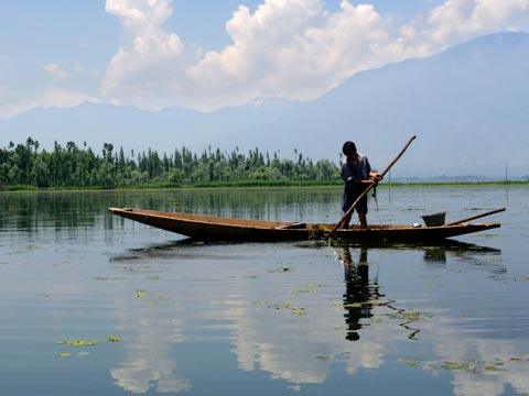 Boy in a small wooden boat punting across a lake in Kashmir with mountain backdrop