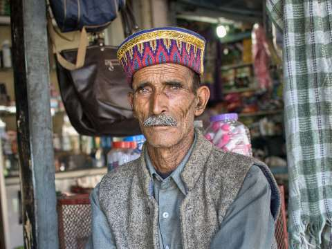 Old man in blue shirt and traditional hat sitting outside his shop in India