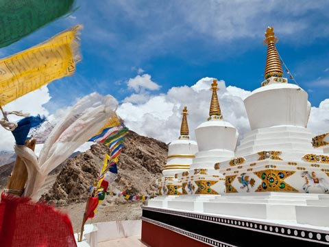White stupas with fluttering multi-coloured prayer flags in Ladakh, India