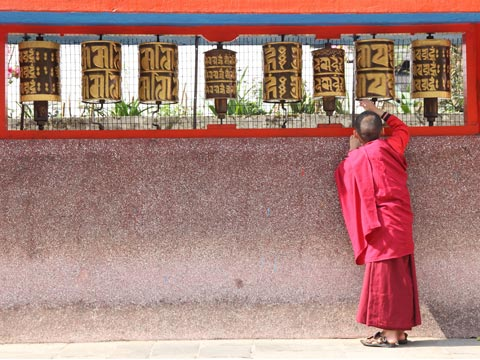 Red-robed monk spinning prayer wheels at a Buddhist temple in India