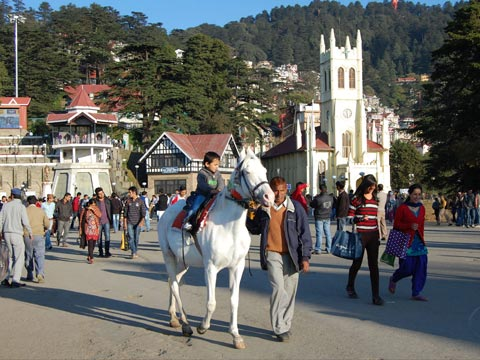 Small boy riding a horse in front of Christ Church in Shimla