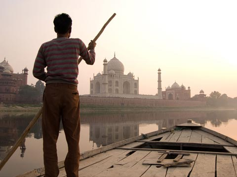 Man in striped top punting wooden boat on river at sunset towards the Taj Mahal