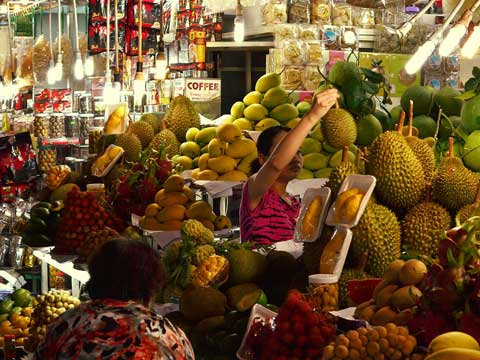 Women at her stall in a nightmarket in Ho Chi Minh City inspecting her produce