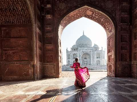 Woman in pink sari standing in a gateway looking at the Taj Mahal in Agra, India