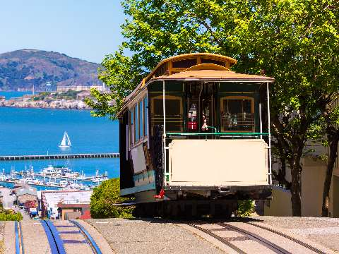 Historic wooden cable car on the top of a San Francisco hill with the bay in the background