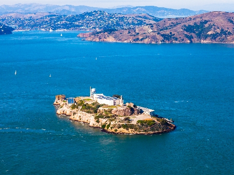 Aerial view of Alcatraz island surrounded by water with hills in background