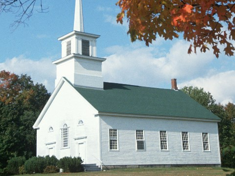 Traditional white wooden church with green roof in New England