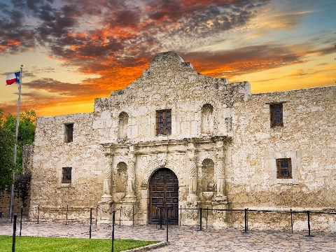 Stone edifice of the Alamo with Texan flag at sunset
