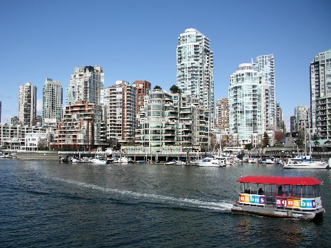 Vancouver skyline with small colourful aqua bus cruising through the harbour