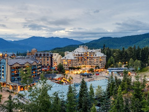 Twilight view of Whistler town with trees and mountains in the background