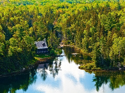 Aerial view of cabin beside a lake surrounded by forest in Canada