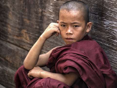 Young novice monk in maroon robes sitting against a temple wall in Burma