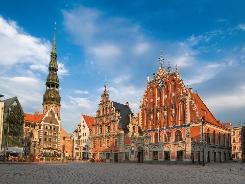 Cobbled square in Riga surrounded by ornate red-brick buildings and a church