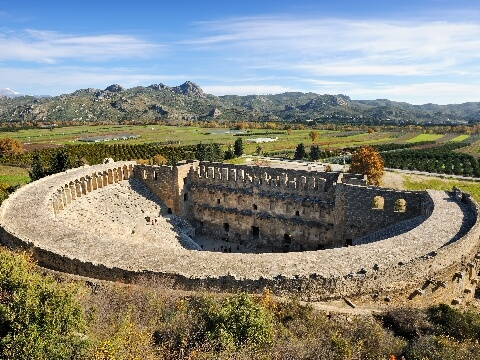 Well preserved Roman amphitheatre surrounded by lush vegetation, Aspendos