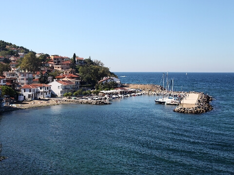 Small stone harbour jutting into the Black Sea with sail boats and small homes clustered on the coast