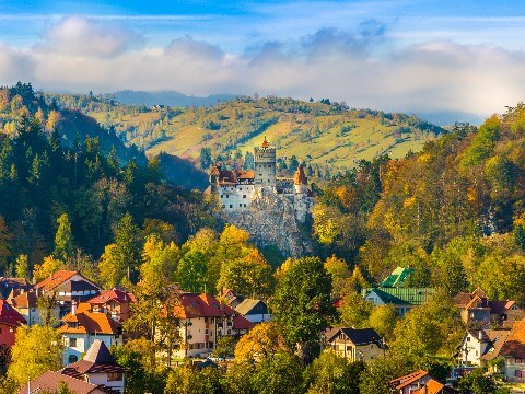 Historic stone castle surrounded by hills, trees and a town in Brasov, Romania