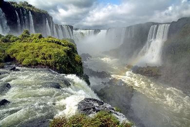 Panoramic view of the large volume of water falling at the Iguacu Falls in Brazil