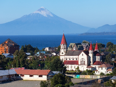 Church with a red spire with snow-capped volcanic peak in distance