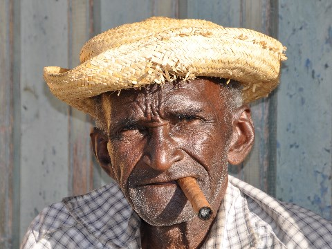 Old Cuban man in a straw hat smoking a cigar