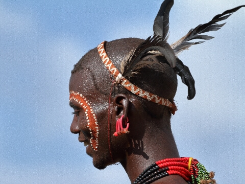 Head shot of Hamar tribesman with painted face decoration and wearing colourful beads and feather headdress