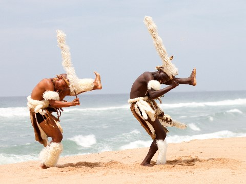 Two zulu men in traditional costume dancing