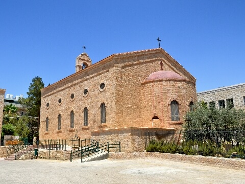 Stone church with arched windows surrounded by trees in Madaba