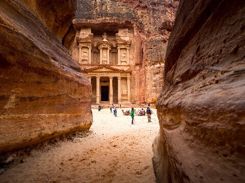 View through narrow canyon to the carved facade of the Treasury at Petra