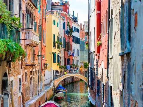 Looking down a narrow canal in Venice with colourful homes either side