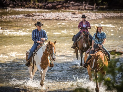 Three people in cowboy clothing riding horses through a river