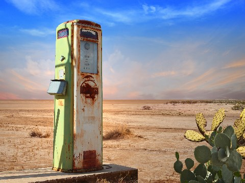 Old and rusty petrol pump surrounded by cacti and desert