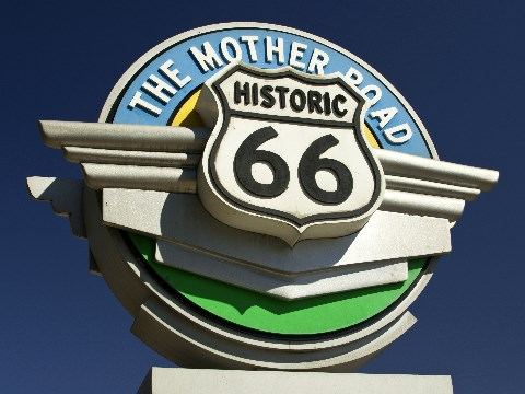Iconic Route 66 sign beside the road with deep blue skies